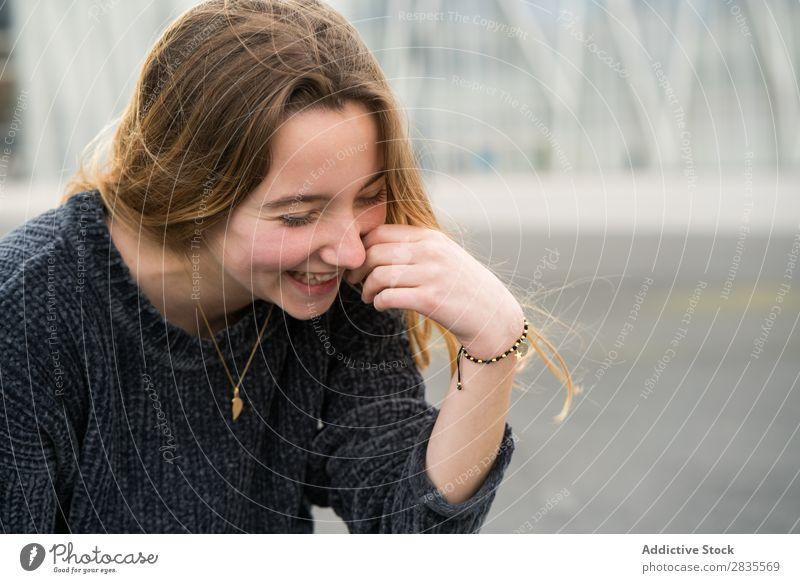 Fröhlich lachendes junges Mädchen Frau hübsch Porträt Jugendliche schön Blick in die Kamera berühren Wange heiter Lächeln Glück Pullover lässig Gesicht