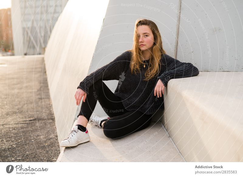 Außenportrait eines jungen Mädchens auf einer Betontreppe mit Blick in die Kamera. Frau Sitzen Klotz Treppe Gebäude verträumt nachdenklich besinnlich
