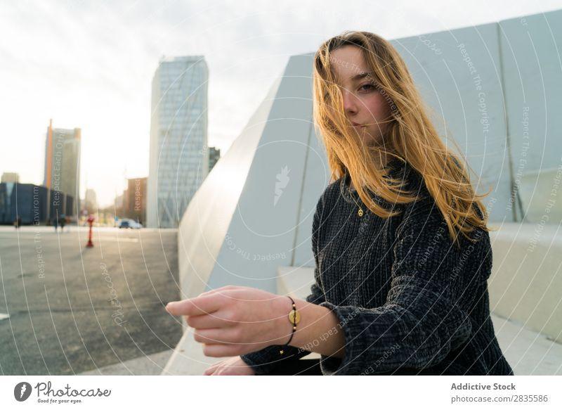 Hübsche junge Frau, die in die Kamera schaut und auf der Straße sitzt. im Freien aufgenommen. Sitzen verträumt nachdenklich besinnlich Wegsehen berührend Lippen