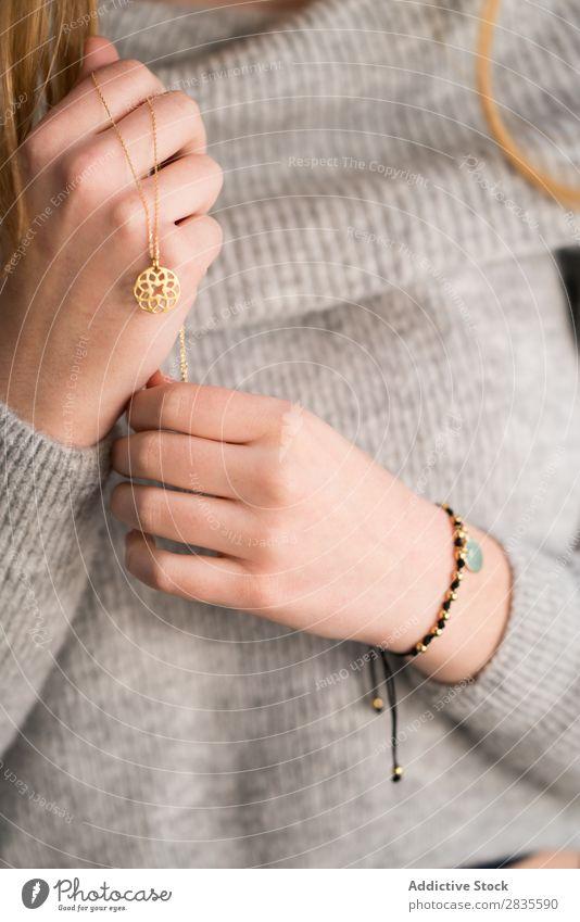 Vertikales Porträt einer jungen Frau, die ihre Halskette berührt. hübsch schön in die Kamera schauen berührend sinnlich verträumt nachdenklich Kragen besinnlich