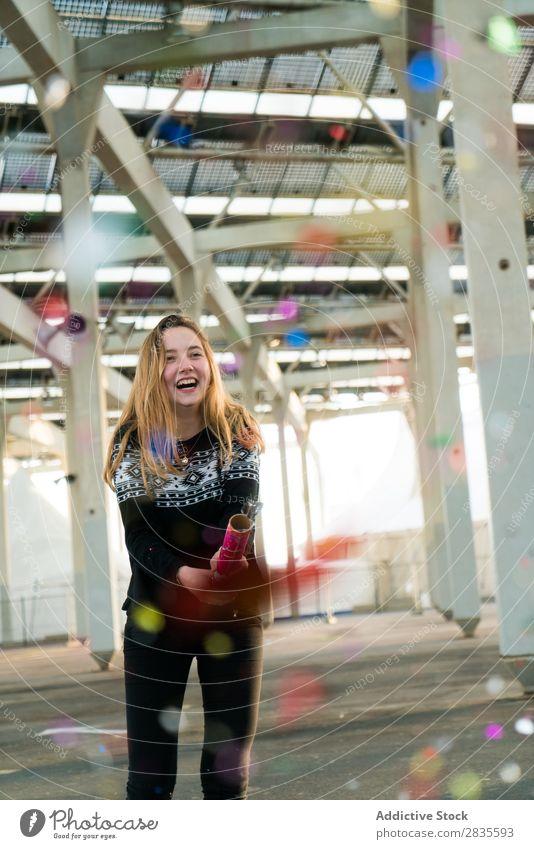 Junge Frau wirft das Konfetti aus sich[Akk] übergeben feiern Spaß farbenfroh hell hübsch Stehen heiter Glück freudig Lächeln Fröhlichkeit jung schön Pullover