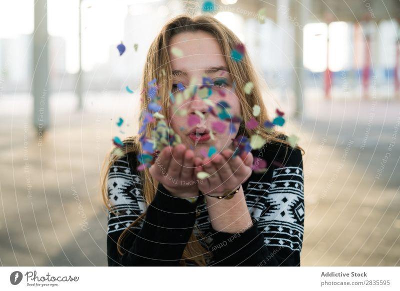 Frau, die das Konfetti bläst. wehen Freude Hand mehrfarbig Blick in die Kamera hell hübsch stehen fliegen Behaarung heiter Glück Lächeln Fröhlichkeit