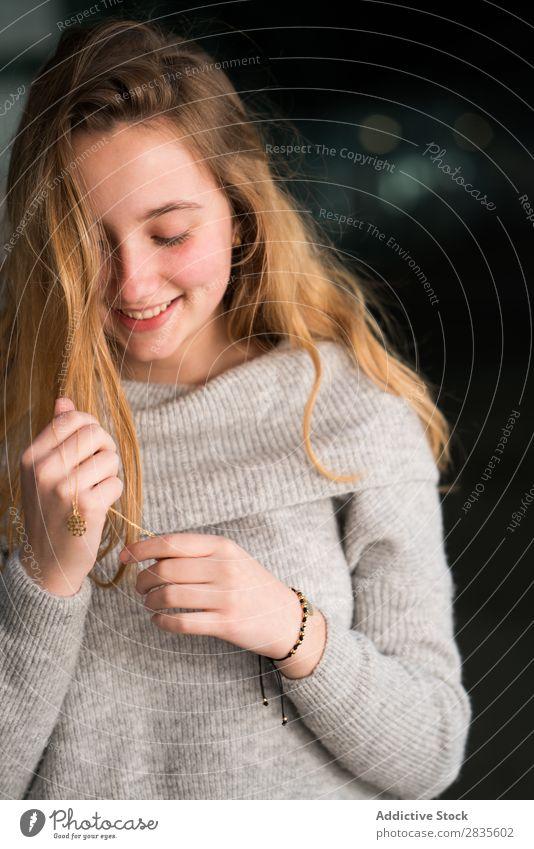Vertikales Porträt einer jungen Frau, die ihre Halskette berührt. hübsch schön herabsehend berührend sinnlich verträumt nachdenklich Kragen besinnlich Pullover