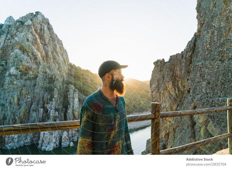 Selbstbewusster Mann auf der felsigen Terrasse Reisender Erholung Klippe Panorama (Bildformat) Körperhaltung selbstbewußt Fernweh Sonnenlicht maskulin