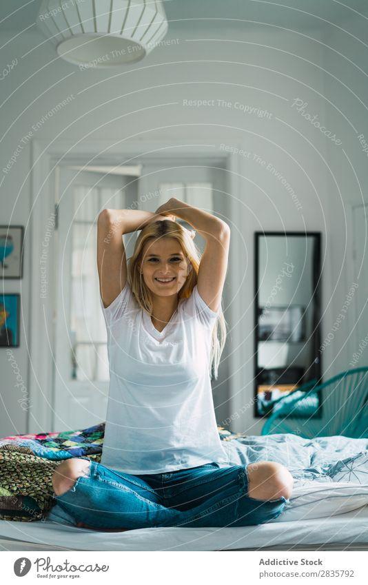 Frau, die sich im Bett dehnt. hübsch heimwärts Jugendliche sitzen strecken wach Blick in die Kamera blond Hände hoch schön Lifestyle Beautyfotografie attraktiv
