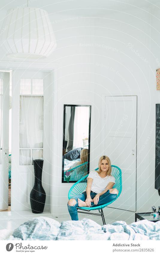 Junge blonde Frau im Stuhl sitzend hübsch heimwärts Jugendliche Blick in die Kamera schön Lifestyle Beautyfotografie attraktiv Porträt Dame Raum Mensch Erholung