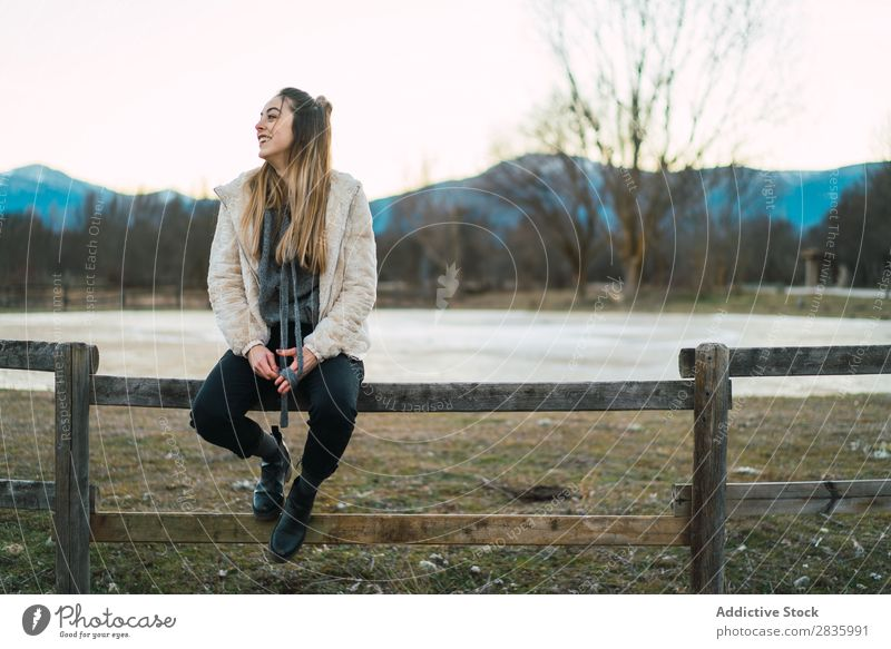 Stylisches junges Mädchen am Zaun auf der Natur Frau Zufriedenheit Landschaft ländlich sitzen heiter Freiheit Unbekümmertheit Kokette Haare & Frisuren