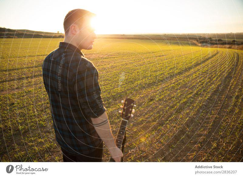 Mann mit Gitarre auf dem Feld Natur Musik stehen Lifestyle Musiker lässig Gitarrenspieler akustisch grün laufen Musical Mensch Typ natürlich Instrument Spielen