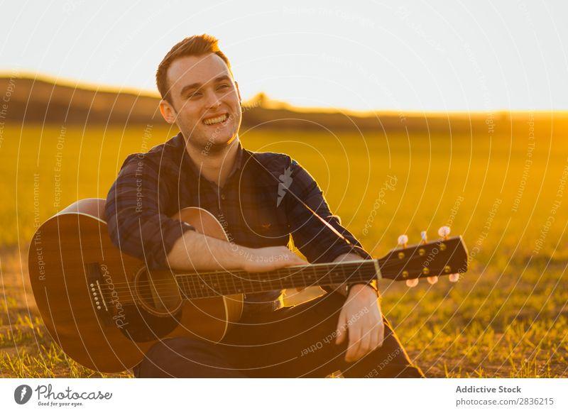 Mann mit Gitarre auf dem Feld Natur Musik Lifestyle Musiker lässig Gitarrenspieler akustisch grün laufen Musical Mensch Typ natürlich Instrument Spielen Stil