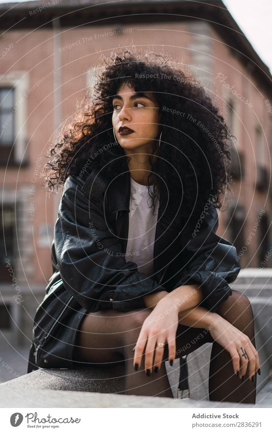Hübsche Frau sitzt auf dem Zaun. attraktiv Großstadt modisch lockig brünett Jacke Mode Jugendliche schön hübsch Straße Model Stil Behaarung Beautyfotografie