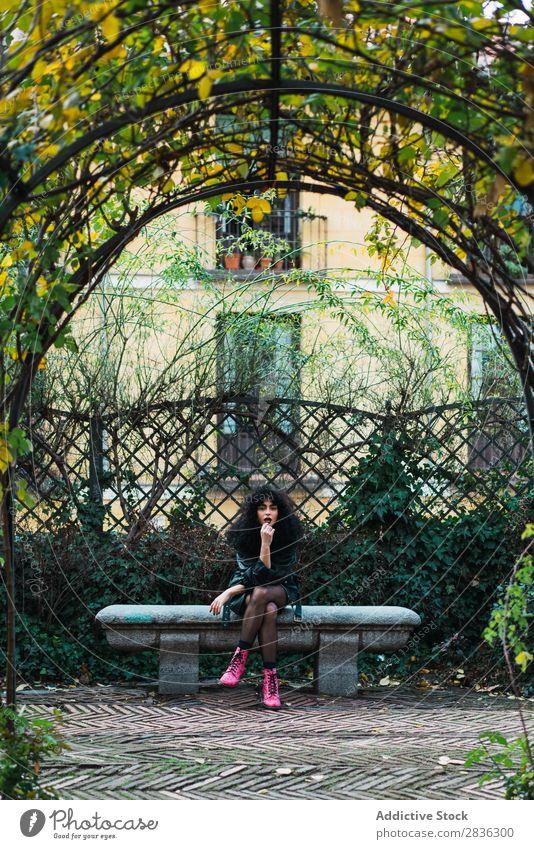 Frau auf dem Zaun im Park attraktiv Großstadt modisch lockig brünett Jacke Mode Jugendliche schön hübsch Straße Model Stil Behaarung Beautyfotografie Dame