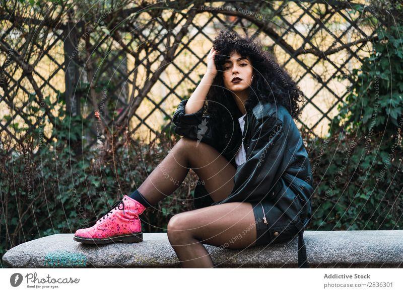 Frau auf dem Zaun im Park attraktiv Großstadt modisch lockig Haltehaar brünett Jacke Mode Jugendliche schön hübsch Straße Model Stil Behaarung Beautyfotografie