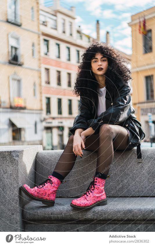 Hübsche Frau sitzt auf dem Zaun. attraktiv Großstadt modisch lockig brünett Jacke Mode Jugendliche schön hübsch Straße Model Stil Blick in die Kamera Behaarung