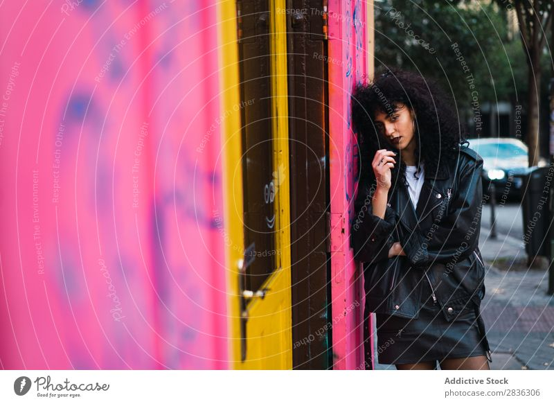 Glamouröse Frau an rosa Wand attraktiv Großstadt modisch lockig anlehnen brünett Jacke Mode Jugendliche schön hübsch Straße Model Stil Behaarung