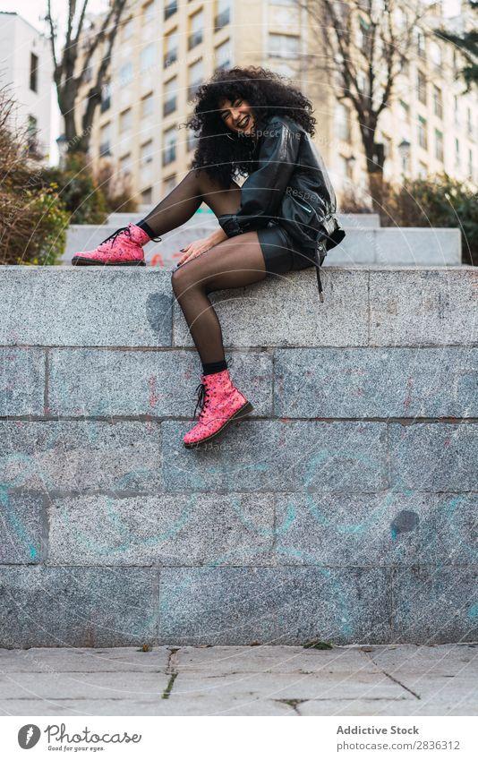 Fröhliche Frau auf der Wand sitzend attraktiv Großstadt modisch lockig brünett Zaun Jacke Mode Jugendliche schön hübsch Straße Model Stil Behaarung