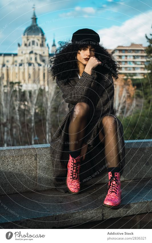 Junge stilvolle Frau, die in der Stadt sitzt. attraktiv Großstadt modisch lockig brünett Mantel Hut sitzen Zaun Aussicht Mode Jugendliche schön hübsch Straße