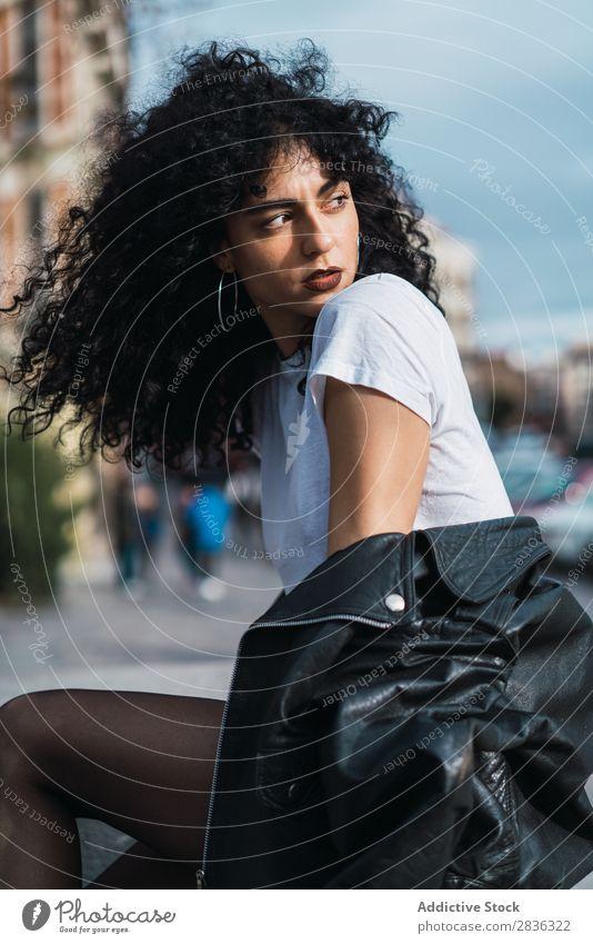 Lockige Frau, die in der Stadt posiert. attraktiv Großstadt modisch lockig brünett Wegsehen Jacke Zaun Mode Jugendliche schön hübsch Straße Model Stil Behaarung