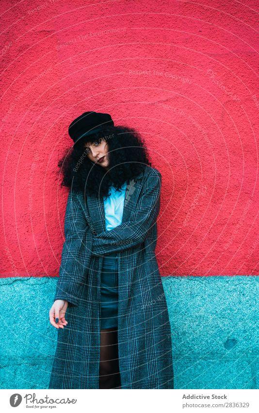 Stylische lockige Frau an bunter Wand attraktiv Großstadt modisch brünett mehrfarbig rot hell Blick in die Kamera Mantel Mode Jugendliche schön hübsch Straße