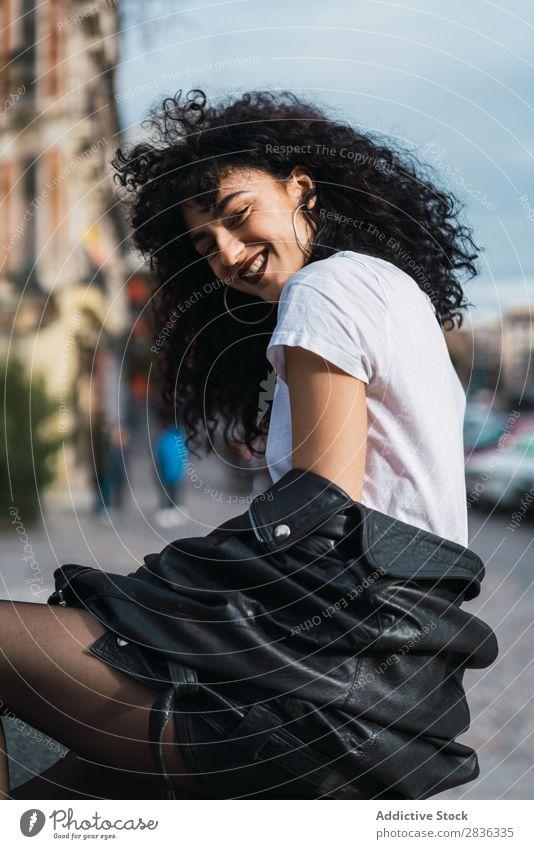 Lockige Frau, die in der Stadt posiert. attraktiv Großstadt modisch lockig brünett Jacke Zaun Mode Jugendliche schön hübsch Straße Model Stil Behaarung