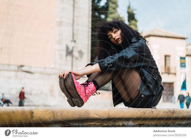 Junge Frau, die am Springbrunnen posiert. attraktiv Großstadt modisch lockig brünett Jacke Wasser Blick in die Kamera Mode Jugendliche schön hübsch Straße Model