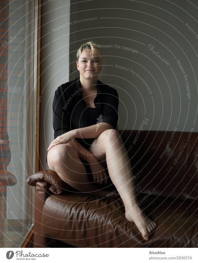 Junge Frau sitzt auf der Couch Stil Freude schön Leben Wohlgefühl Wohnung Raum Jugendliche Beine 18-30 Jahre Erwachsene Barfuß blond kurzhaarig Fenster Sofa