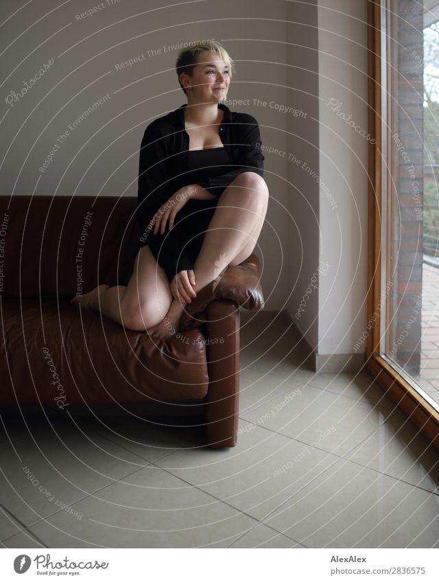 Junge Frau sitzt auf der Couch schön Wohlgefühl Wohnung Raum Fenster Jugendliche Beine 18-30 Jahre Erwachsene Barfuß blond kurzhaarig Lächeln sitzen ästhetisch