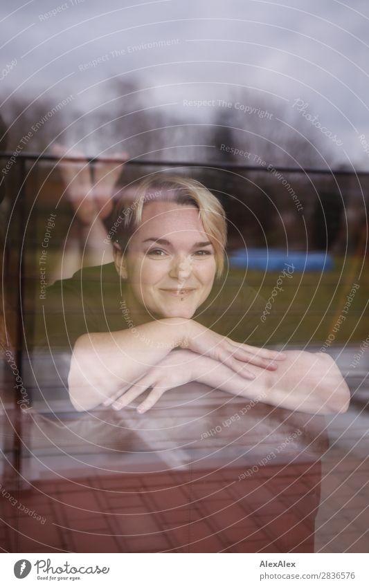 Junge Frau hinterm Fenster liegt auf der Couch Freude schön Leben Wohlgefühl Wohnung Raum Jugendliche 18-30 Jahre Erwachsene blond kurzhaarig Lächeln liegen
