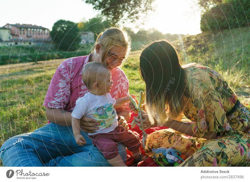 Glückliche Familie im Park Mutter Kind Rasen grün Sonnenstrahlen Mensch Frau Fröhlichkeit Sommer Lifestyle Liebe gleichgeschlechtliche Eltern Homosexualität