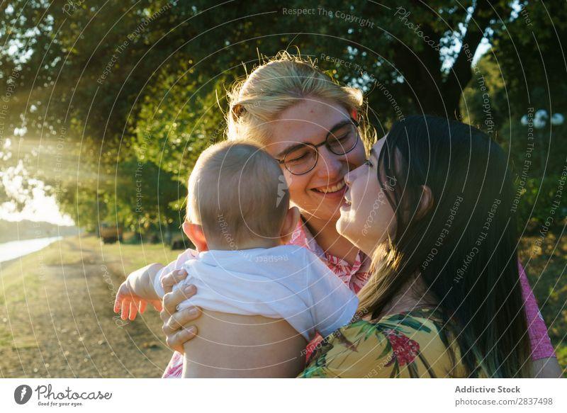 Glückliches lesbisches Paar mit Kind Mutter Park grün Sonnenstrahlen Mensch Frau Fröhlichkeit Sommer Lifestyle Liebe gleichgeschlechtliche Eltern Homosexualität