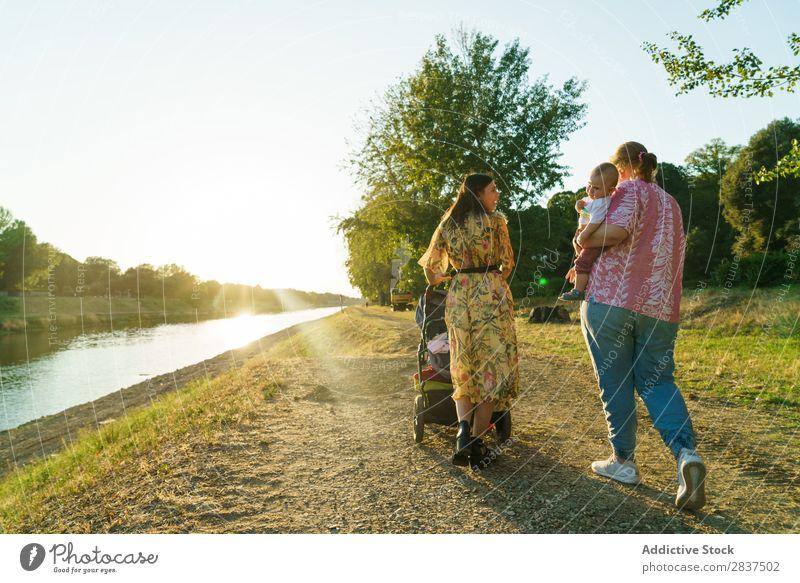Lesbisches Paar mit Kind im Park Mutter laufen Wagen grün Sonnenstrahlen Glück Mensch Frau Fröhlichkeit Sommer Lifestyle Liebe gleichgeschlechtliche Eltern