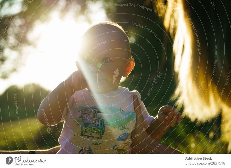 Süßes kleines Kind im Park Rasen grün Mutter Sonnenstrahlen Familie & Verwandtschaft Glück Mensch Frau Fröhlichkeit Sommer Lifestyle Liebe Eltern Natur