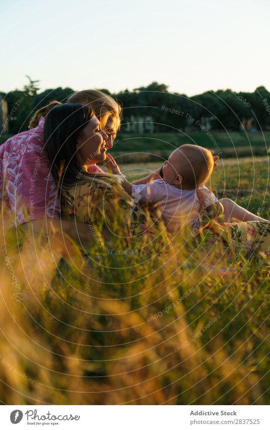 Glückliche lesbische Familie mit Kind Mutter Park Rasen grün Sonnenstrahlen Mensch Frau Fröhlichkeit Sommer Lifestyle Liebe gleichgeschlechtliche Eltern
