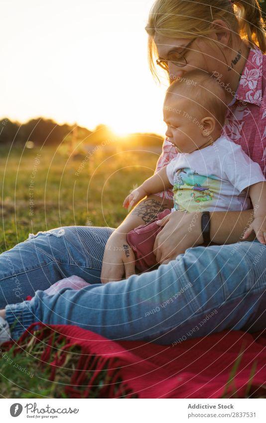 Frau mit Kind auf dem Rasen Mutter Park grün Sonnenstrahlen Glück Mensch Fröhlichkeit Sommer Lifestyle Liebe gleichgeschlechtliche Eltern Homosexualität Paar