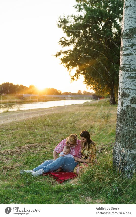 Lesbische Familie mit Kind auf dem Rasen Mutter Park grün Sonnenstrahlen Glück Mensch Frau Fröhlichkeit Sommer Lifestyle Liebe gleichgeschlechtliche Eltern