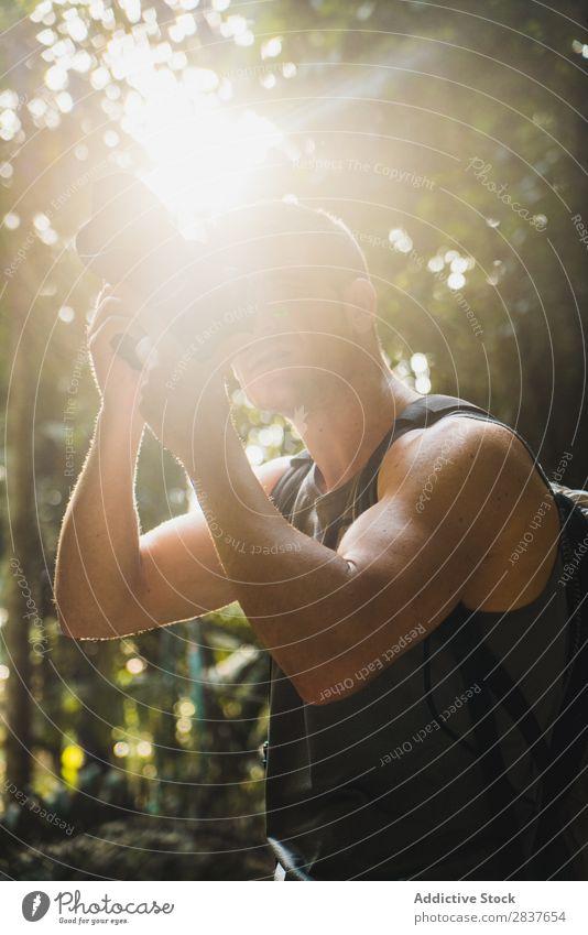 Ein Mann, der im Dschungel schießt. Fotograf Urwald Tourist Erwachsene Fokussierung zielen professionell Ferien & Urlaub & Reisen Wald Natur Tourismus