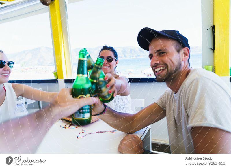 Junge Freunde, die mit Bier klirren. Mensch Freundschaft Party Feste & Feiern Zuprosten Gratulation Café Sammeln klirrend Ferien & Urlaub & Reisen heiter