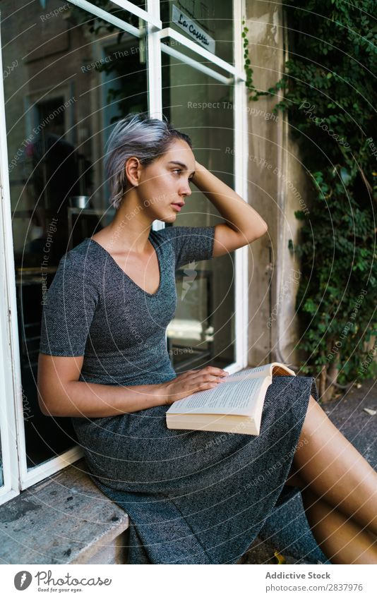 Frau liest Buch am Fenster Straße sitzen Fenstersims schön