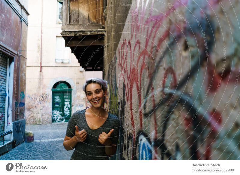 Lächelnde Frau in der Gasse Graffiti Wand hübsch Straße Lifestyle heiter ruhig Erholung blond laufen lieblich attraktiv Dame Großstadt Jugendliche Mensch