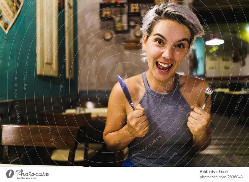 Wütendes Mädchen, das mit Silberwaren posiert. Frau Restaurant Appetit & Hunger Spaß haben Wut Ausdruck Gesichtsbehandlung Gefühle humorvoll hysterisch Café