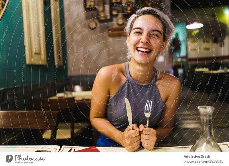 Wütendes Mädchen, das mit Silberwaren posiert. Frau Restaurant Appetit & Hunger Spaß haben Ausdruck Gesichtsbehandlung Gefühle humorvoll hysterisch Wut Café