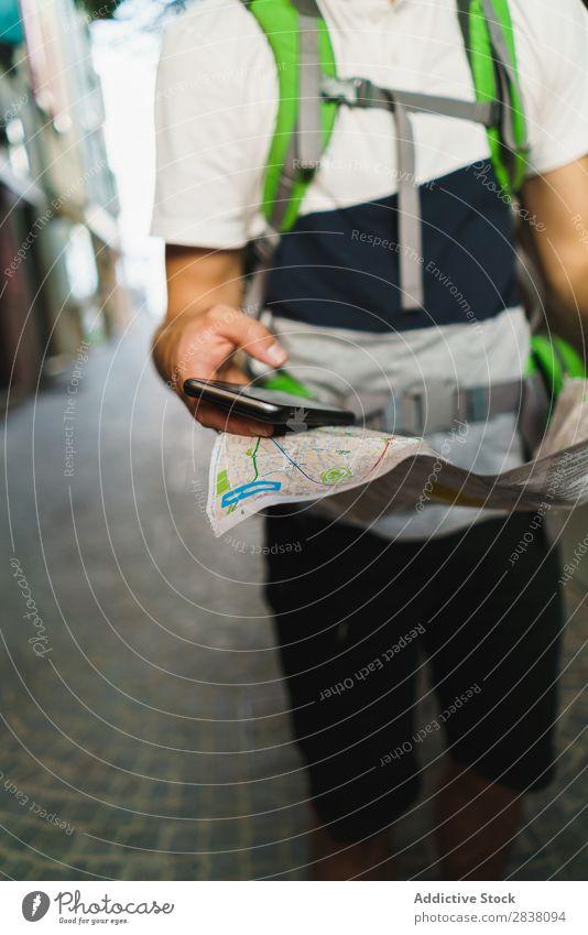 Mann mit Telefon und Karte beschneiden Rucksacktourismus Tourismus PDA Landkarte Gps Großstadt Orientierung Richtung Backpacker Stadt Apparatur Aktion Internet