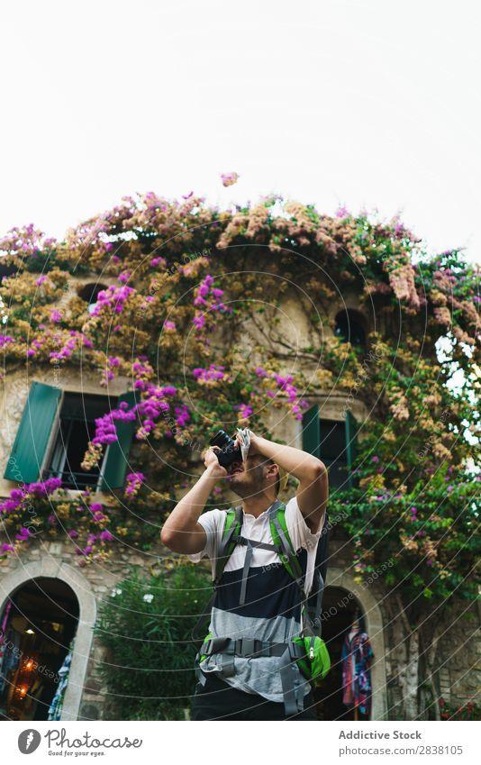 Mann fotografiert Umgebung in der Stadt Backpacker Tourist fotografierend Erinnerung romantisch Fotograf Fotokamera Straße reisend Großstadt Lifestyle