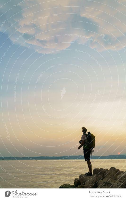 Backpacker, der auf Felsen posiert. Mann Reisender Körperhaltung Aktion Sommer Jugendliche Abenteuer Meer Landschaft Großstadt so tun, als ob lustig Sport