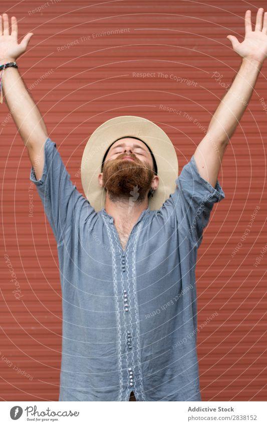 Glücklicher Mann, der an der Wand posiert. bärtig Stil Körperhaltung Fürsorge Jugendliche Haare & Frisuren gutaussehend maskulin Aussehen vertikal lässig