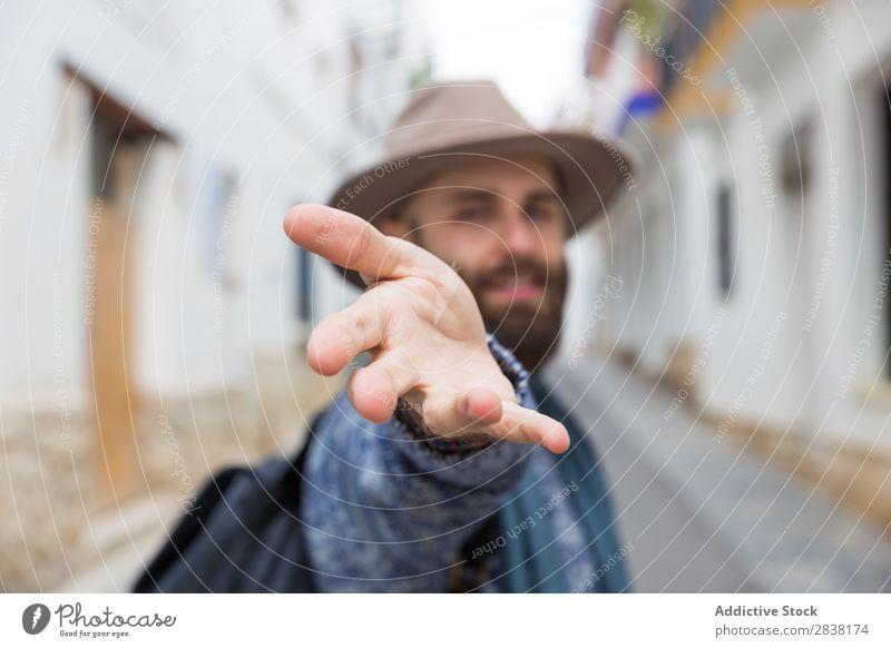 Fröhlicher bärtiger Mann, der auf die Kamera schaut und mir mit Gesten folgt. Tourist mir folgen gestikulieren Blick in die Kamera gutaussehend Lächeln Hand