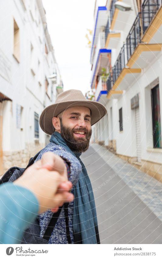 Mann hält die Hand des Fotografen. Tourist mir folgen gestikulieren Blick in die Kamera bärtig gutaussehend Lächeln gestikulierend Ferien & Urlaub & Reisen