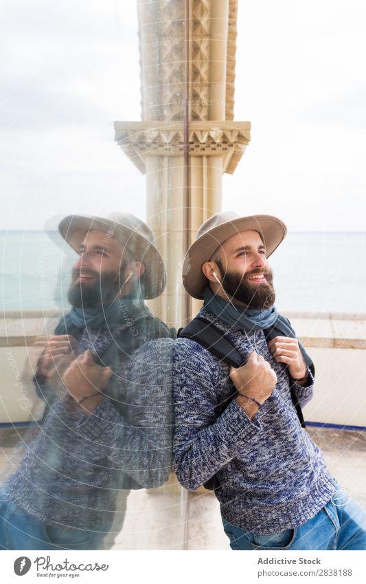 Fröhlicher bärtiger Mann mit Kopfhörer Stil Wegsehen Lächeln Ferien & Urlaub & Reisen Tourist Glück heiter Porträt stehen Musik Jugendliche Lifestyle Hut