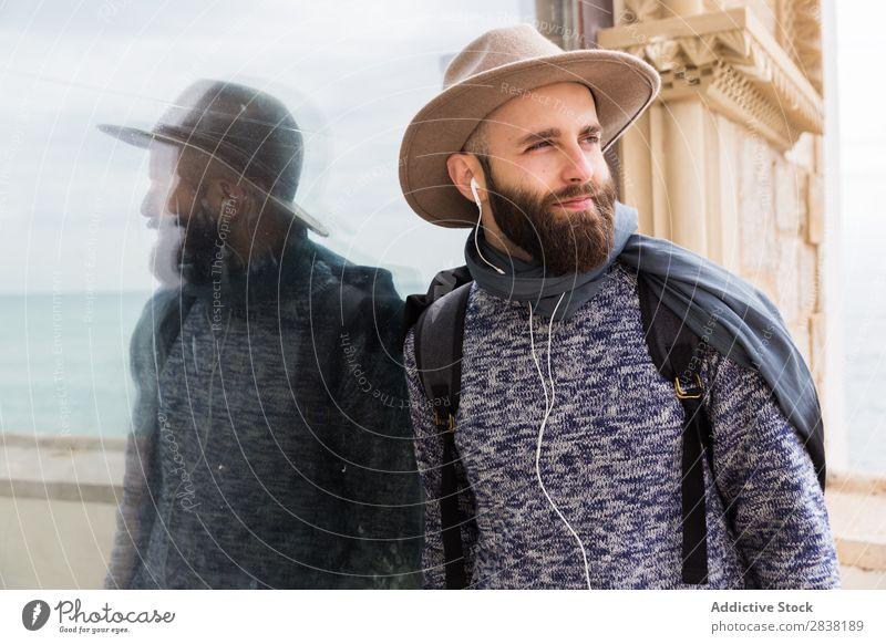 Fröhlicher bärtiger Mann hört Musik. Kopfhörer Stil Blick in die Kamera heiter Zufriedenheit Porträt stehen Jugendliche Lifestyle Hut gutaussehend Typ lässig