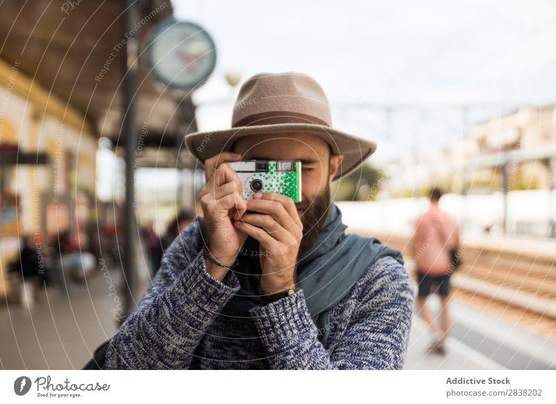 Mann macht Aufnahmen mit einer kleinen Kamera. Fotograf lässig Tourismus Eisenbahn Station Ferien & Urlaub & Reisen Fotokamera Tourist Reisender zielen