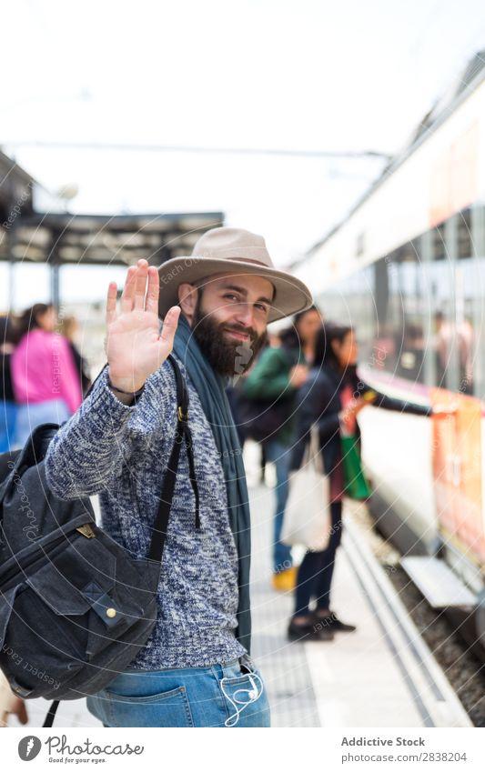 Fröhlicher Tourist am Bahnhof Mann Eisenbahn Station Begrüßung gestikulieren Abschied Blick in die Kamera Ferien & Urlaub & Reisen Verkehr Ausflug Rucksack